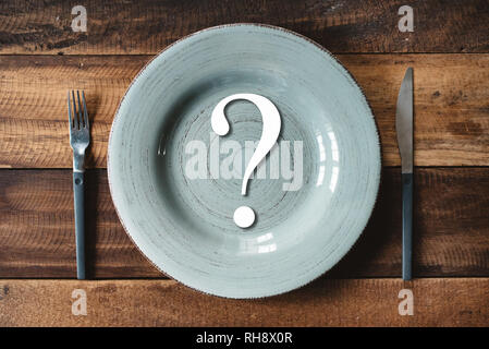 top view of a table set of cutlery with symbol of question mark in a plate. concept off diet and where or what to eat. - Stock Image