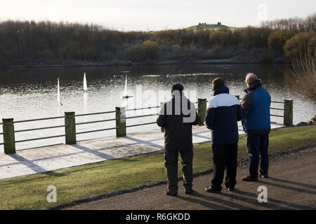 Men sailing model yachts in Herrington Country Park on a frosty day, Sunderland, England, UK - Stock Image