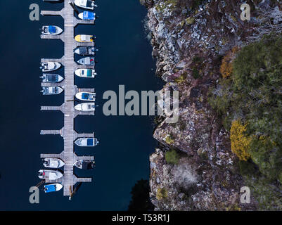 Aerial overhead view of a wooden boat dock next to a rocky seaside cliff - Stock Image