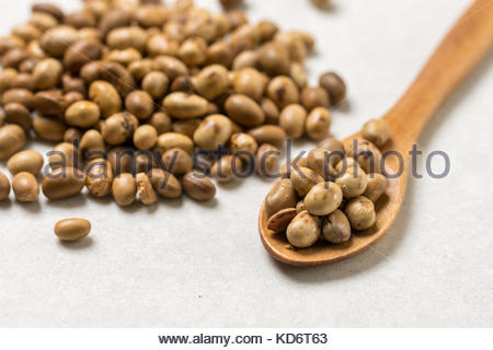 Pile of soya beans with wooden spoon on the white marble background table. - Stock Image