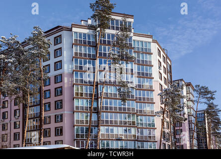 Multi-storey residential building among the snow-covered tops of pines. The facade of the house is visible through tall trees in the snow. Lots of sno - Stock Image