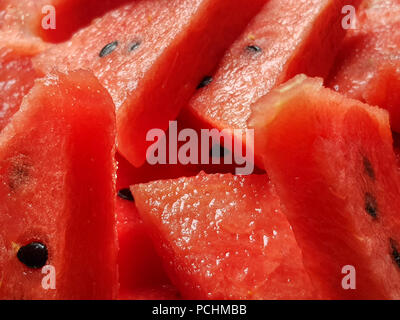 Many slices of red ripe and juicy watermelon as full frame background - Stock Image