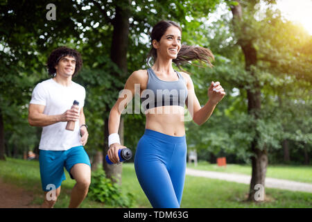 Happy couple running and jogging together outdoor - Stock Image