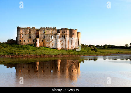 A view of Carew castle, Pembrokeshire, wales, UK. Taken in the evening in golden sunlight with the castle reflected - Stock Image