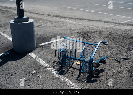 overturned broken shopping cart in parking lot - Stock Image