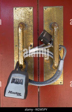 A doorway is secured with heavy metal cable land multiple locks - Stock Image