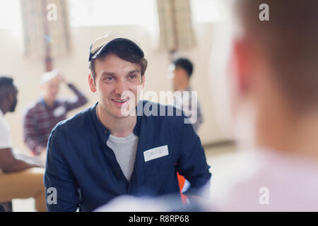 Smiling man listening in group therapy - Stock Image