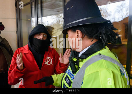 London, UK. 6th April 2019. After Class War had pushed aside the barriers the protest continued on the steps of the Dorchester Hotel in Mayfair against the multi-billionaire Sultan of Brunei who has announced death by stoning as a punishment for gay sex, adultery and blasphemy demonstrating against this barbaric abuse of international law and human rights and calling for a boycott of his hotels around the world. The doors were locked and the protesters made only token efforts to enter the hotel, blocking the entrance with a noisy protest on the steps. Police talk sternly to an anarchist protes - Stock Image