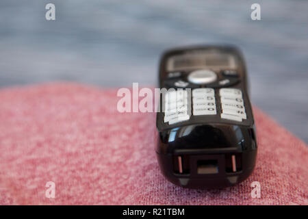 A black cordless phone sits waiting to be picked up or dialed - Stock Image