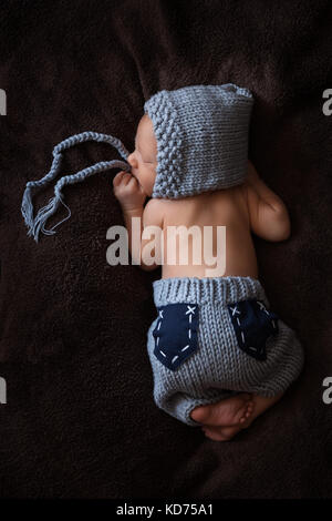 Newborn baby in a gray knitted suit sleeps in a beautiful pose - Stock Image