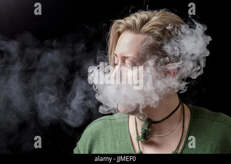 Young adult female exhaling smoke from electronic cigarette - Stock Image