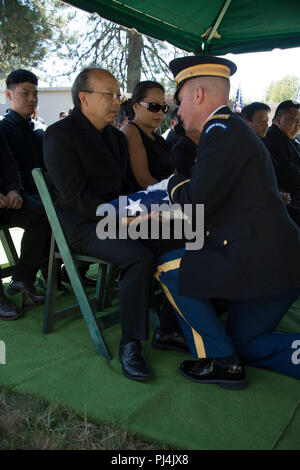 California Army National Guard officer Capt. Steven Lily hands off the flag of   Major Gen (Ret.) Nhia Bee Lee, to his brother Serge Lee At the Sierra memorial lawn in Nevada City California. This is the first time US honors were presented to a Hmong General who fought on the side of the US during Vietnam. - Stock Image