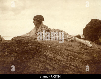 Woman lying on a rock at the seaside. - Stock Image