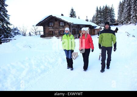 Three persons with sledge in snow, Ammergau Alps, Allgaeu, Bavaria, Germany, Europe - Stock Image