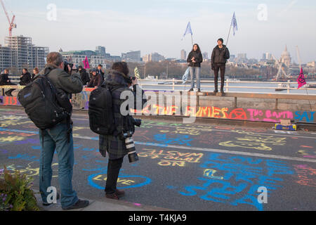Photographers take pictures of two protestors on Waterloo Bridge for the Extinction Rebellion demonstration with the City of London behind - Stock Image