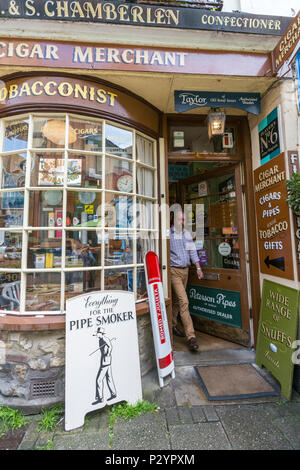 Man leaving the C&S Chamberlen: Tobacconists and Cigar Merchants at George street at Hastings old town, East Sussex, England , UK - Stock Image