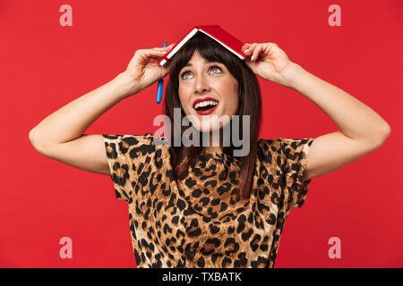 Image of a beautiful young woman dressed in animal printed shirt posing isolated over red background with notebook on head. - Stock Image