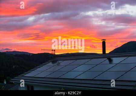 Sunset over solar panels on a house roof in Ambleside, Lake District, UK. - Stock Image