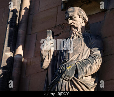 A statue of Saint Andrew one of the many  ornate carved figures of kings, queens and saints around Lichfield Cathedral. - Stock Image
