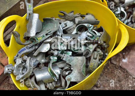 Pile of scaffolding coupler clamps on the ground used on a building site - Stock Image