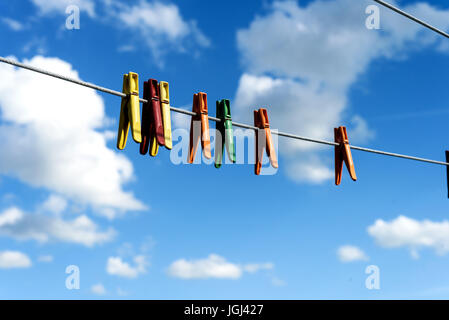 An assortment of brightly colored washing pegs and clothespins on a outdoor washing line with bright blue sky and - Stock Image
