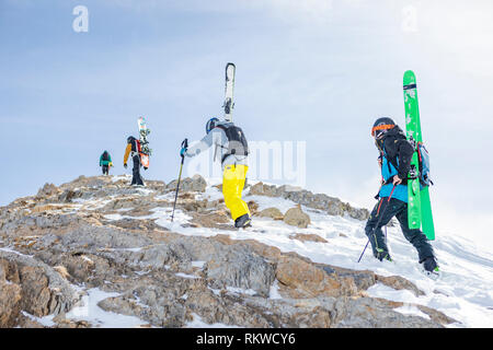 Skiers and snow boarders hiking to the summit of La Capa on a powder day. - Stock Image