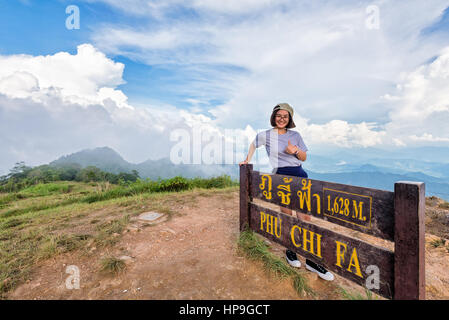 Tourist teen girl hiker wear cap and glasses standing smile pose thumb up near nameplate attractions of Phu Chi - Stock Image