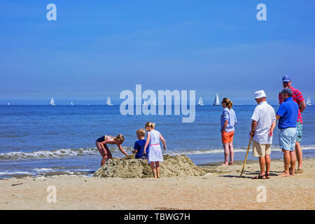 Parents and grand-parents on the beach watching little children building sand castle along the North Sea coast - Stock Image
