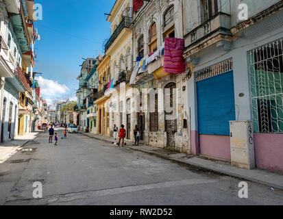 A family plays football in the dilapidated back streets of Havana, capital of Cuba - Stock Image