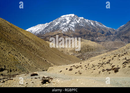 Dirt track leading to the village of Ghemi, partly visible in the distance. Upper Mustang region, Nepal. - Stock Image