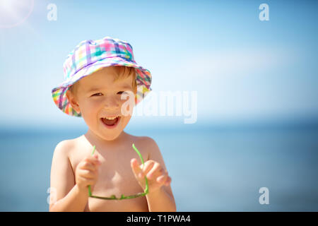 three years old boy smiling at the beach in hat with sunglasses. Child on vacations at sea - Stock Image