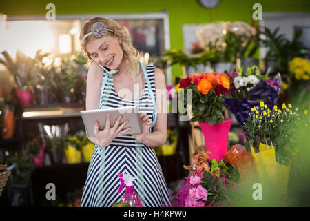 Female florist talking on mobile phone and using digital tablet - Stock Image