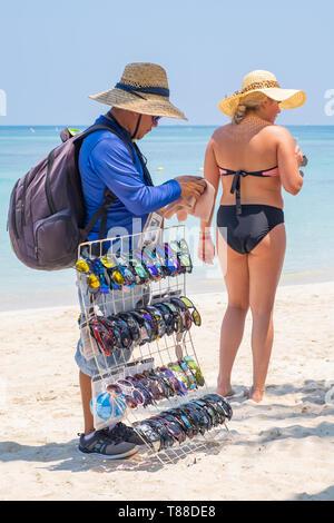 Male beach vendor sells sunglasses to the tourists at West Bay Roatan Honduras. - Stock Image