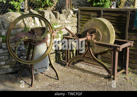 Redundant old hand operated farm implements. A root chopping machine and a tool sharpening sandstone wheel.On a farm in the Purbeck peninsula, Dorset, - Stock Image