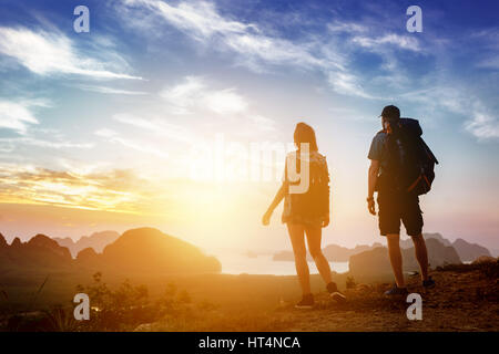 Hikers backpacks mountain top view sunrise - Stock Image