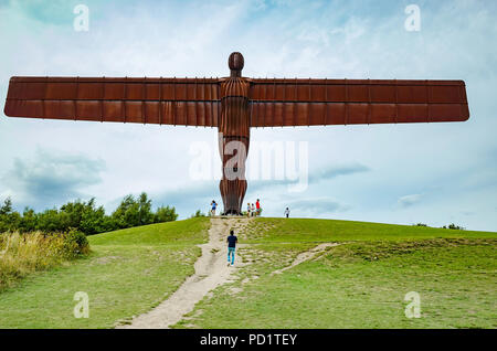 A group of people at the foot of the massive Angel of the North sculpture by Anthony Gormley  at Gateshead giving scale - Stock Image