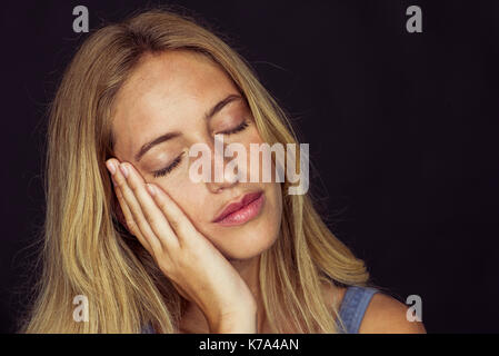 Young woman resting cheek on hand, eyes closed, portrait - Stock Image