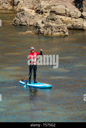 Dunbar, East Lothian, Scotland, UK. 21st Apr 2019. UK Weather:  People enjoy the very sunny hot Easter day weather at Eye Cave cove. A paddle board instructor with Coast to Coast surf school - Stock Image
