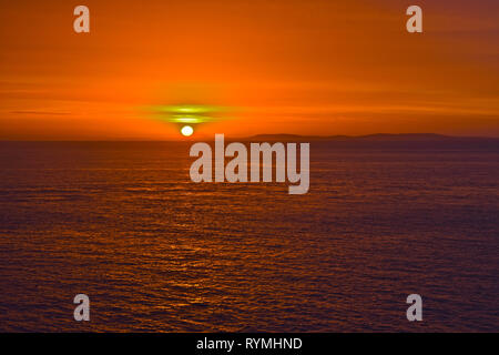 A beautiful sunrise on a Winter's day in Tenby, with the sun climbing above the distant hills of the Gower Peninsular. - Stock Image