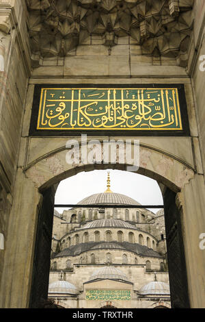 Entrance to Blue Mosque in Istanbul, Turkey. More than 32 million tourists visit Turkey each year. Text: There is no god but Allah, and Muhammad is hi - Stock Image