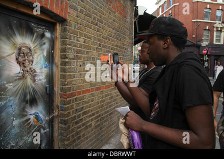 London 3 August 2013.  South African youth seen taking photos of the portrait of 'Madiba' on Brick Lane. - Stock Image