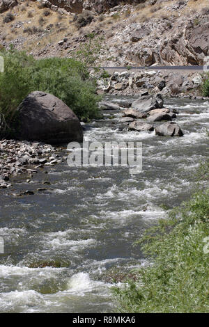 A river runs through a rocky, barren, desert landscape surrounded by thriving plant life in the western USA - Stock Image