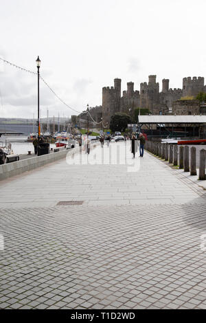 View along the quay at Conwy (Conway) in North Wales with fishing and leisure boats at anchor and Conwy Castle in the background - Stock Image