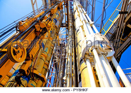 Low angle view of pipes and cables on offshore oil platform - Stock Image