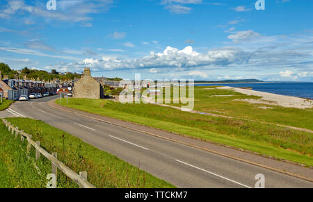 PORTGORDON MORAY SCOTLAND THE ROAD LEADING INTO THE VILLAGE WITH HOUSES THE BEACH AND THE SEA - Stock Image