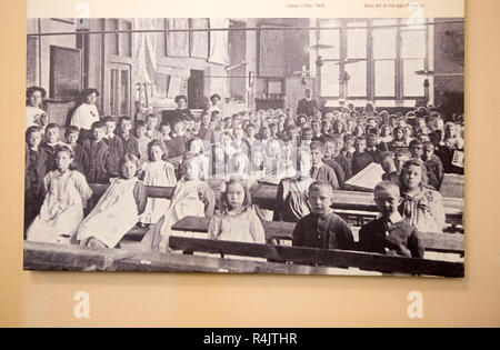 Wooden desks in school classroom from early 1900s, Radstock museum, Somerset, England, UK old monochrome photograph 1908 - Stock Image