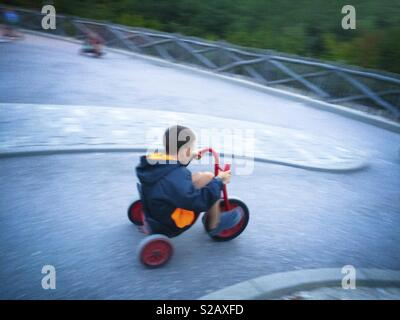 Boy riding a little three wheeler bike - Stock Image