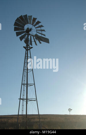 windmills silhouetted against blue sky in barren paddock, Queensland, Australia. Windmills are commonly used for - Stock Image