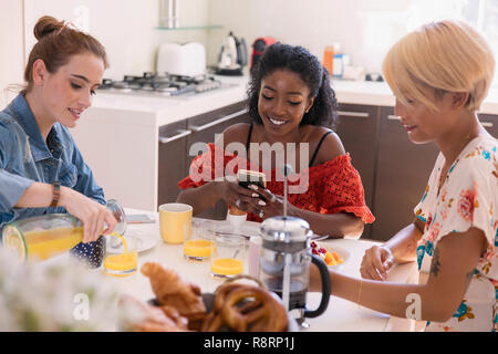 Young women friends enjoying breakfast at kitchen table - Stock Image