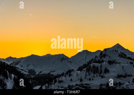 Yellow skies at sunset over the mountains in Obertauern, Austria - Stock Image